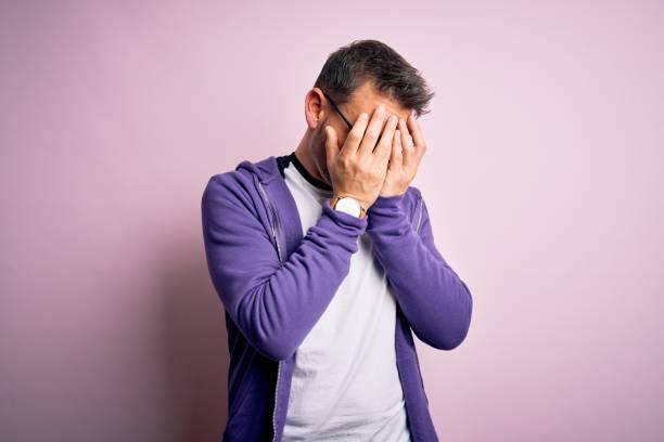 joven hombre guapo con sudadera púrpura y gafas de pie sobre fondo rosa con expresión triste cubriendo la cara con las manos mientras llora. concepto de depresión. - vergüenza fotografías e imágenes de stock