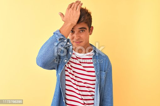 1046559700istockphoto Young handsome man wearing striped t-shirt and denim shirt over isolated yellow background surprised with hand on head for mistake, remember error. Forgot, bad memory concept. 1173766395
