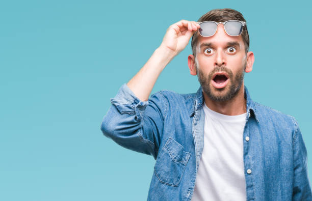 young handsome man wearing sunglasses over isolated background afraid and shocked with surprise expression, fear and excited face. - sorpresa foto e immagini stock