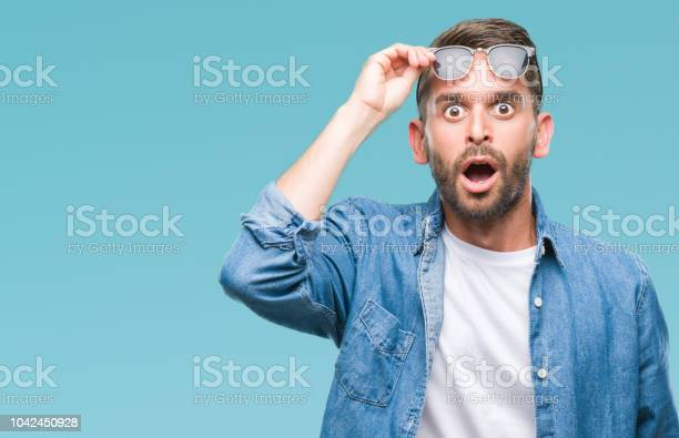 Photo of Young handsome man wearing sunglasses over isolated background afraid and shocked with surprise expression, fear and excited face.