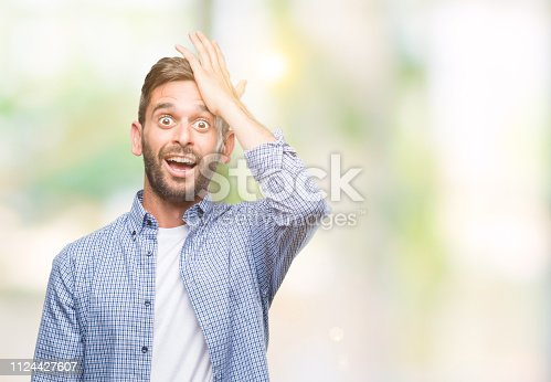 1046559700istockphoto Young handsome man wearing white t-shirt over isolated background surprised with hand on head for mistake, remember error. Forgot, bad memory concept. 1124427607