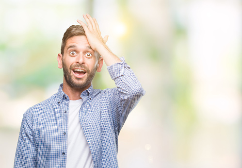 1046559700 istock photo Young handsome man wearing white t-shirt over isolated background surprised with hand on head for mistake, remember error. Forgot, bad memory concept. 1124427607