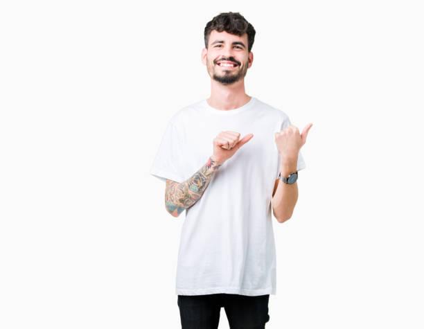 schöner junger mann mit weißen t-shirt über isoliert hintergrund auf der rückseite hinter mit hand und daumen hoch, lächelt zuversichtlich - junger mann stock-fotos und bilder