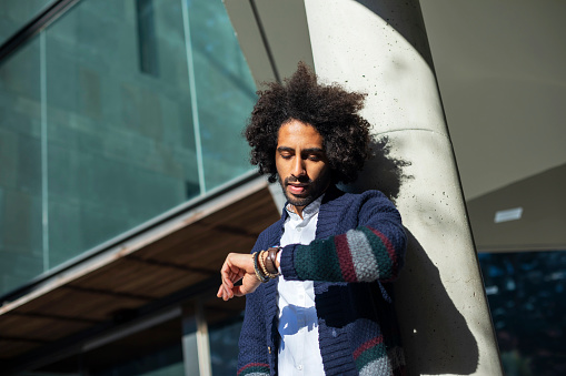 istock Young handsome man with afro hair Checking the time on wrist watch 1178593191