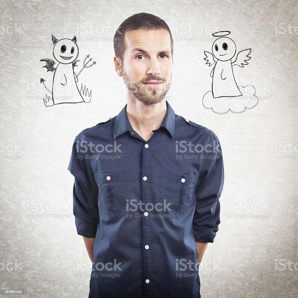 Young handsome man with angel and devil stock photo