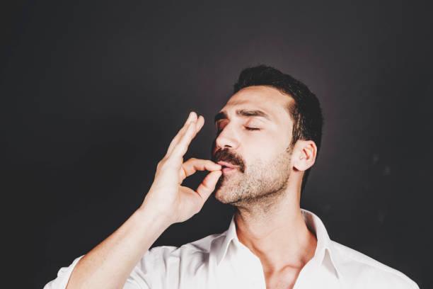 schönen jungen mann mit bart und schnurrbart studioportrait - gestikulieren stock-fotos und bilder