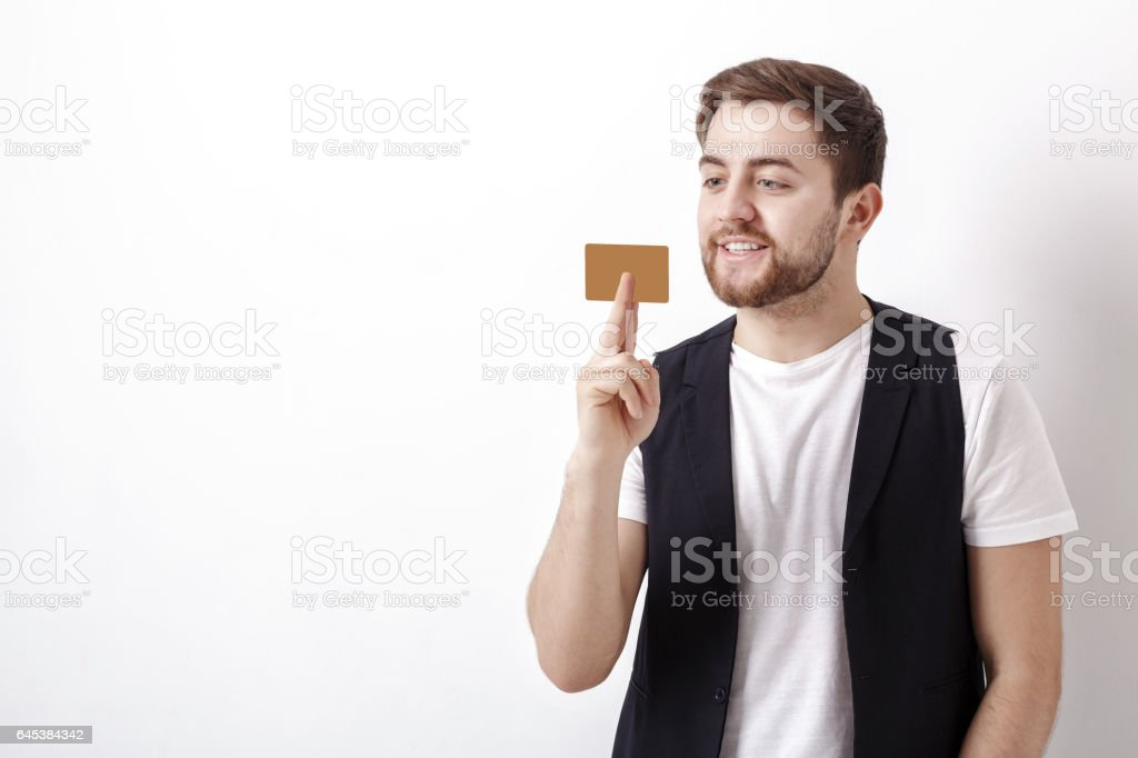young handsome man with beard in white shirt and black waistcoat holding plastic credit card and smiling stock photo