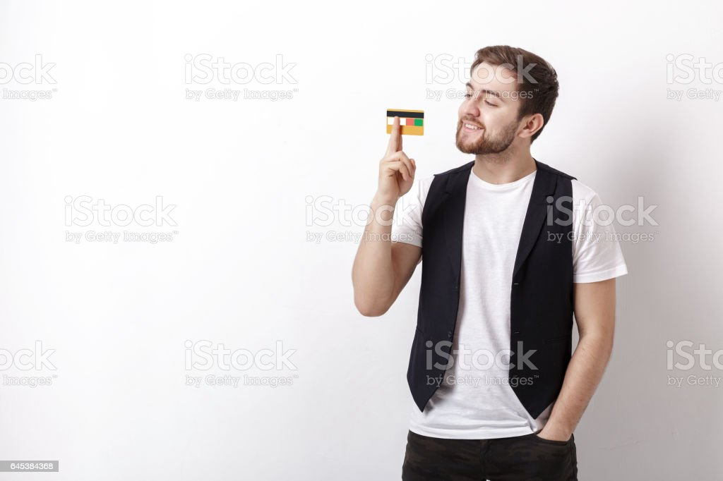young handsome man with beard in white shirt and black waistcoat showing plastic credit card and smiling stock photo