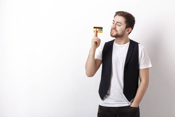 young handsome man with beard in white shirt and black waistcoat showing plastic credit card and smiling - lustige grußkarten stock-fotos und bilder
