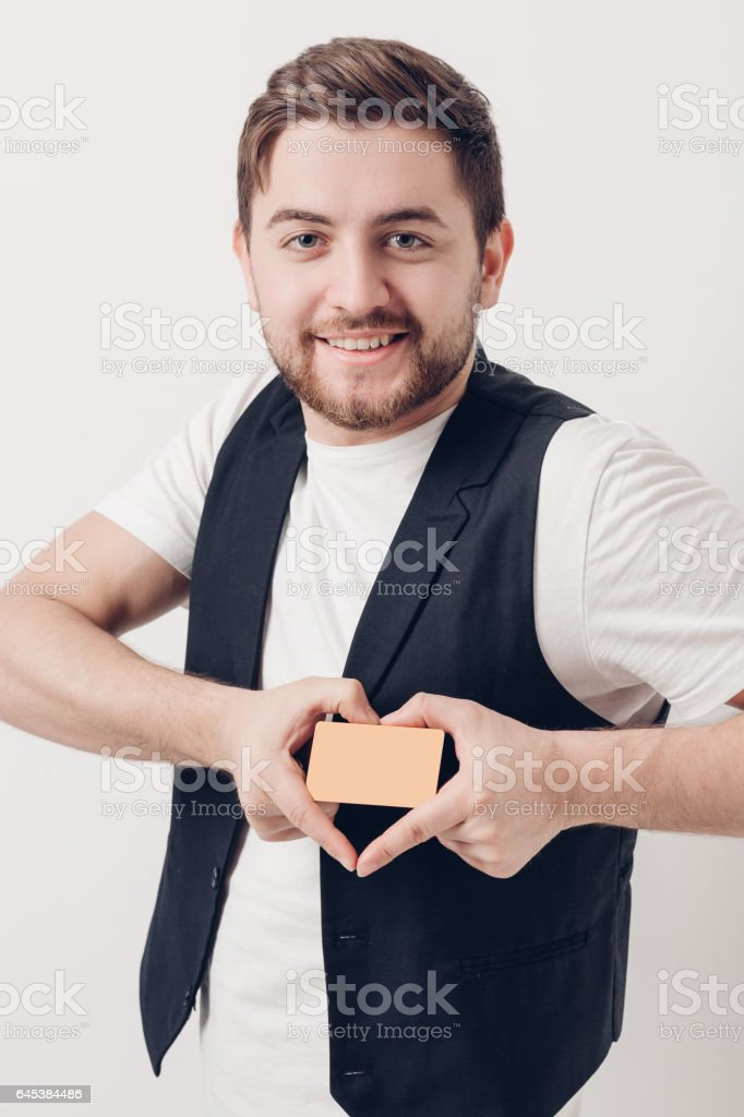 young handsome man with beard in white shirt and black waistcoat holding plastic credit card and smiling. soft light stock photo