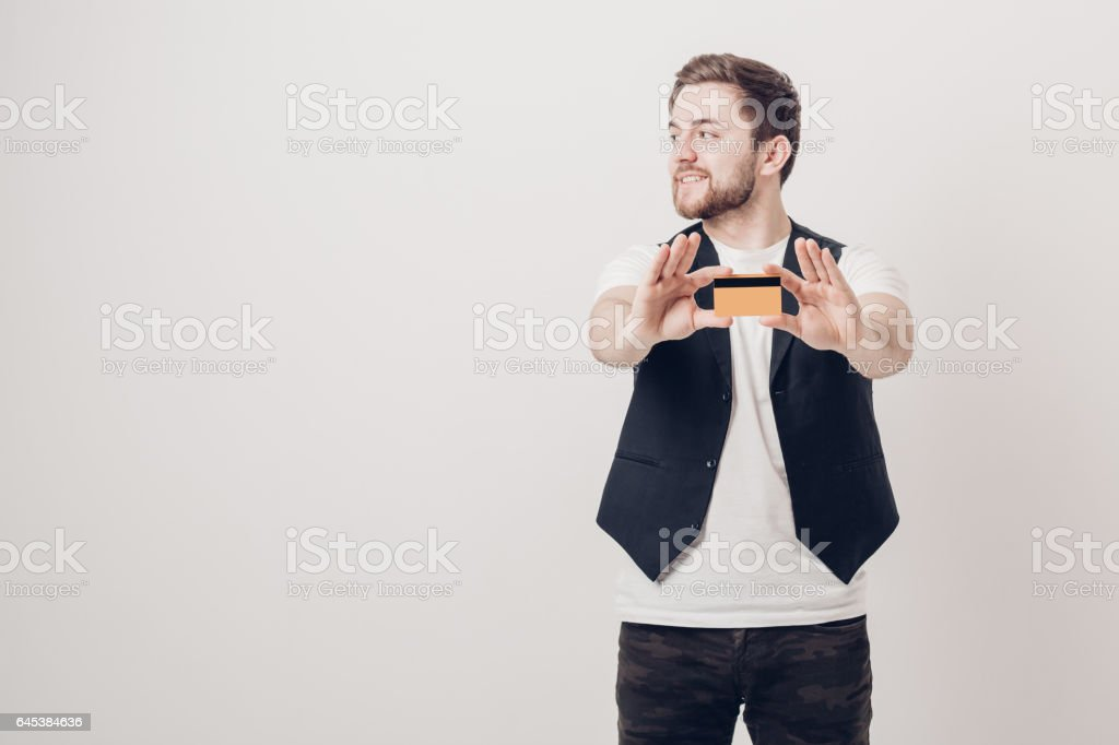 young handsome man with beard in white shirt and black waistcoat holding plastic credit card and smiling. focus on card. soft light stock photo