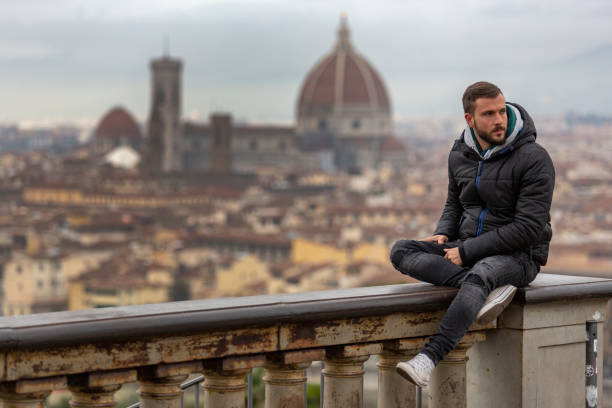 A young handsome man with beard sitting on a wall in a viewpoint of Florence, Italy stock photo