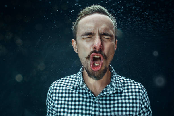 Young handsome man with beard sneezing, studio portrait stock photo