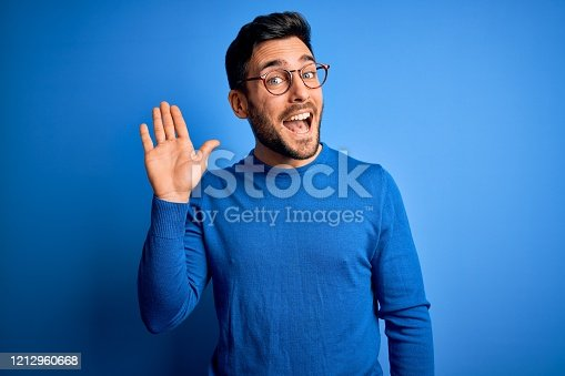 Young handsome man with beard wearing casual sweater and glasses over blue background Waiving saying hello happy and smiling, friendly welcome gesture