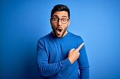 istock Young handsome man with beard wearing casual sweater and glasses over blue background Surprised pointing with finger to the side, open mouth amazed expression. 1212960962