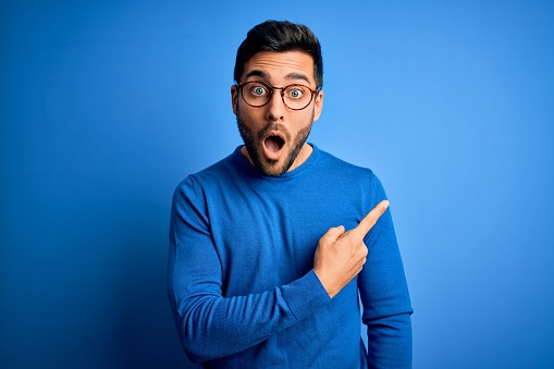Young handsome man with beard wearing casual sweater and glasses over blue background Surprised pointing with finger to the side, open mouth amazed expression.