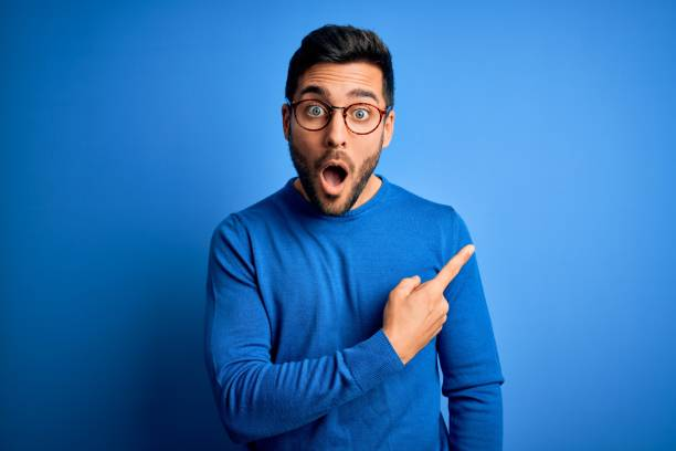 Young handsome man with beard wearing casual sweater and glasses over blue background Surprised pointing with finger to the side, open mouth amazed expression. stock photo