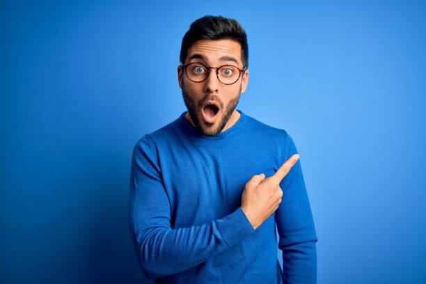 jonge knappe mens met baard die toevallige sweater en glazen over blauwe achtergrond draagt verrast die met vinger aan de kant, open mond verbaasde uitdrukking richt. - verrassing stockfoto's en -beelden