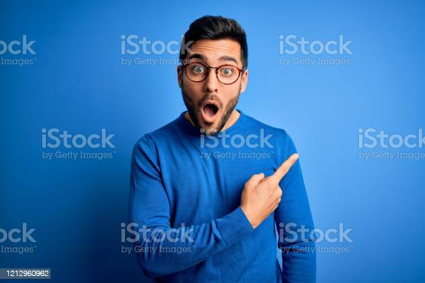 Photo of Young handsome man with beard wearing casual sweater and glasses over blue background Surprised pointing with finger to the side, open mouth amazed expression.