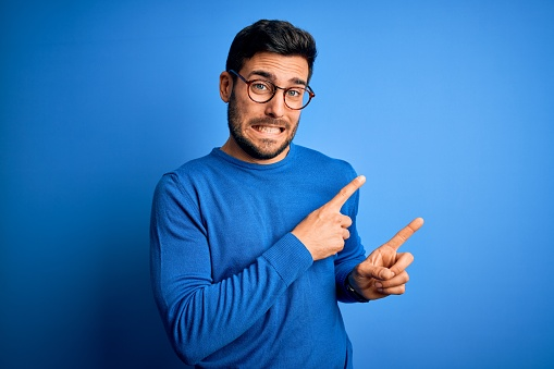Young handsome man with beard wearing casual sweater and glasses over blue background Pointing aside worried and nervous with both hands, concerned and surprised expression