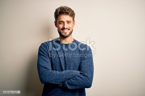 Young handsome man with beard wearing casual sweater standing over white background happy face smiling with crossed arms looking at the camera. Positive person.
