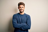 istock Young handsome man with beard wearing casual sweater standing over white background happy face smiling with crossed arms looking at the camera. Positive person. 1212702108