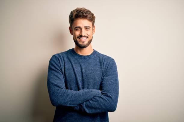 jeune homme beau avec la barbe utilisant le chandail occasionnel restant au-dessus du visage heureux blanc de fond souriant avec les bras croisés regardant la caméra. personne positive. - homme photos et images de collection