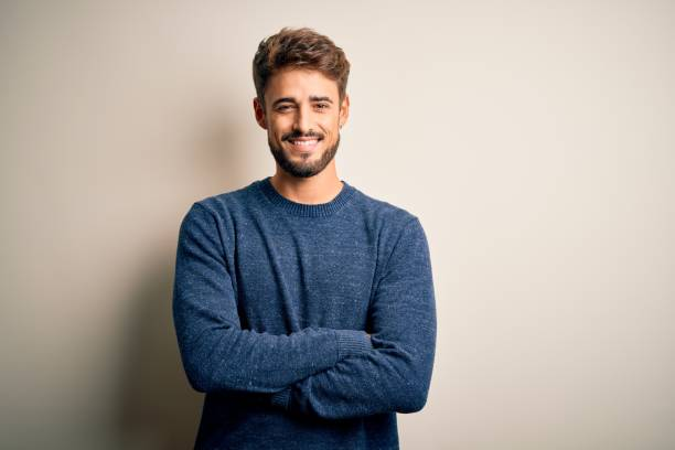 Young handsome man with beard wearing casual sweater standing over white background happy face smiling with crossed arms looking at the camera. Positive person. stock photo