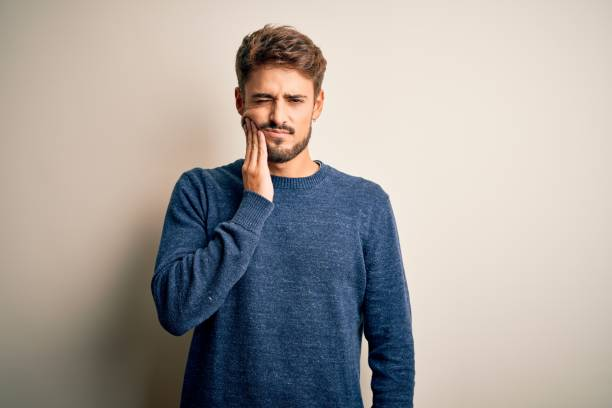 Young handsome man with beard wearing casual sweater standing over white background touching mouth with hand with painful expression because of toothache or dental illness on teeth. Dentist stock photo