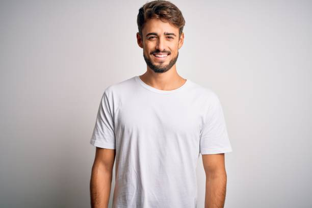 Young handsome man with beard wearing casual t-shirt standing over white background with a happy and cool smile on face. Lucky person. stock photo