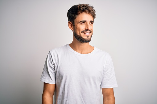 Young handsome man with beard wearing casual t-shirt standing over white background looking away to side with smile on face, natural expression. Laughing confident.