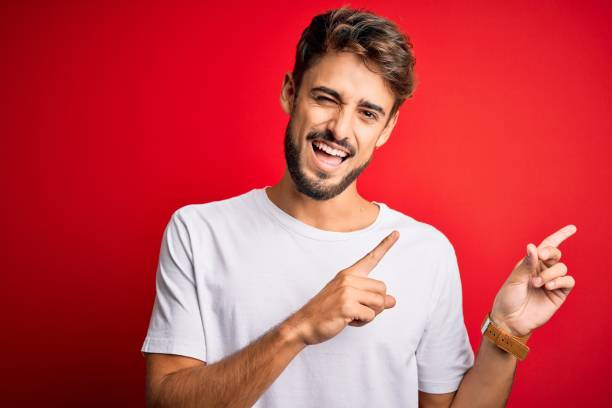 Young handsome man with beard wearing casual t-shirt standing over red background smiling and looking at the camera pointing with two hands and fingers to the side. stock photo