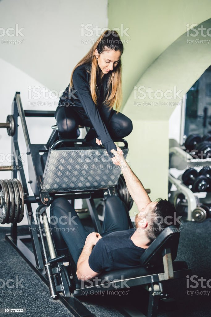 Young handsome man with his girlfriend exercise legs in the gym. royalty-free stock photo