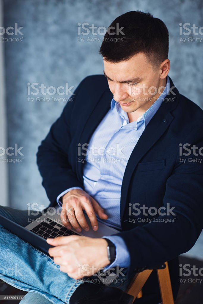 Young handsome man with laptop computer looking at screen stock photo