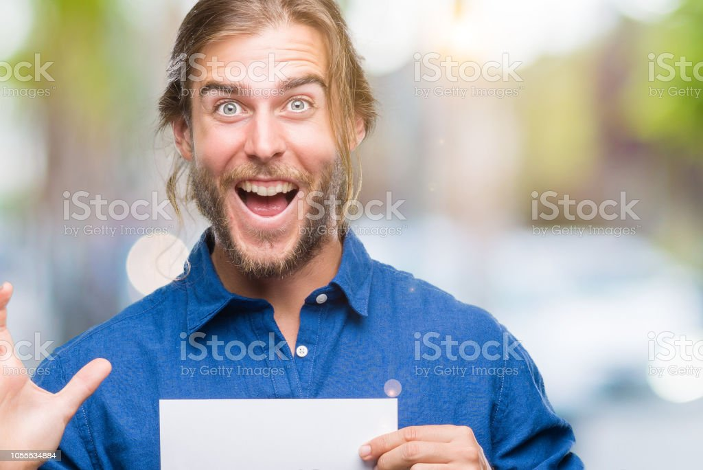 Young handsome man with long hair over isolated background holding blank paper very happy and excited, winner expression celebrating victory screaming with big smile and raised hands stock photo
