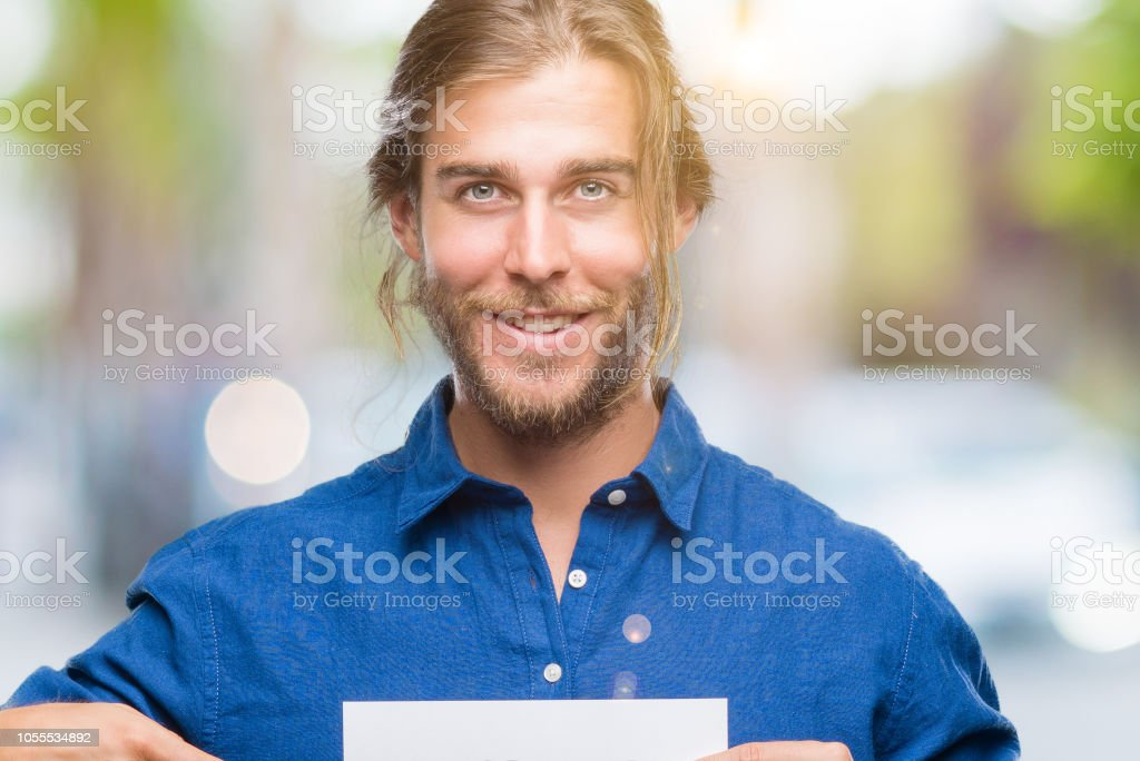 Young handsome man with long hair over isolated background holding blank paper very happy pointing with hand and finger stock photo