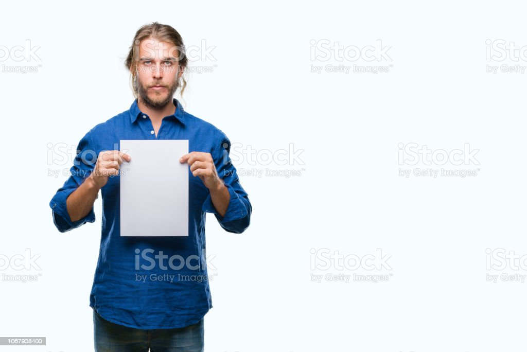 Young handsome man with long hair over isolated background holding blank paper with a confident expression on smart face thinking serious stock photo