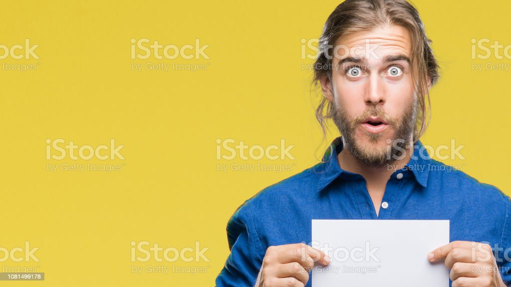 Young handsome man with long hair over isolated background holding blank paper scared in shock with a surprise face, afraid and excited with fear expression stock photo