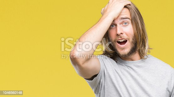 1046559700istockphoto Young handsome man with long hair over isolated background surprised with hand on head for mistake, remember error. Forgot, bad memory concept. 1046560148