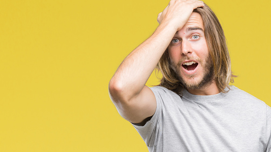 1046559700 istock photo Young handsome man with long hair over isolated background surprised with hand on head for mistake, remember error. Forgot, bad memory concept. 1046560148