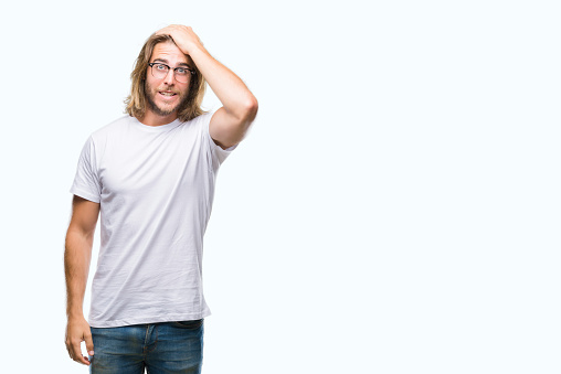 1046559700 istock photo Young handsome man with long hair wearing glasses over isolated background surprised with hand on head for mistake, remember error. Forgot, bad memory concept. 1043195040