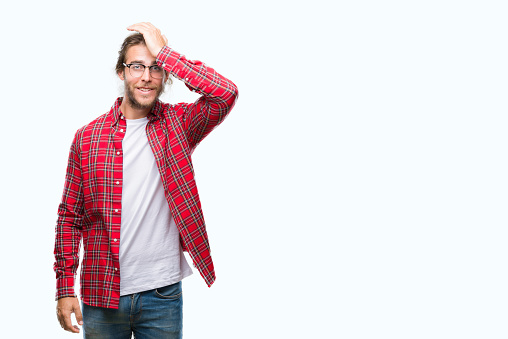1046559700 istock photo Young handsome man with long hair wearing glasses over isolated background surprised with hand on head for mistake, remember error. Forgot, bad memory concept. 1043195232