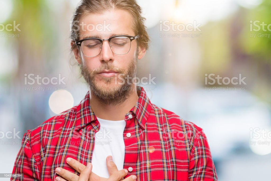 9278c55a Young handsome man with long hair wearing glasses over isolated background  smiling with hands on chest