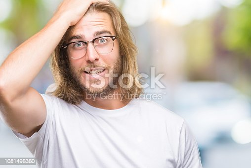 1046559700istockphoto Young handsome man with long hair wearing glasses over isolated background surprised with hand on head for mistake, remember error. Forgot, bad memory concept. 1081496360