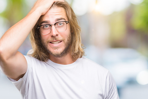 1046559700 istock photo Young handsome man with long hair wearing glasses over isolated background surprised with hand on head for mistake, remember error. Forgot, bad memory concept. 1081496360