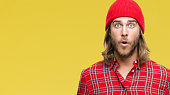 istock Young handsome man with long hair wearing red cap over isolated background afraid and shocked with surprise expression, fear and excited face. 1055535562