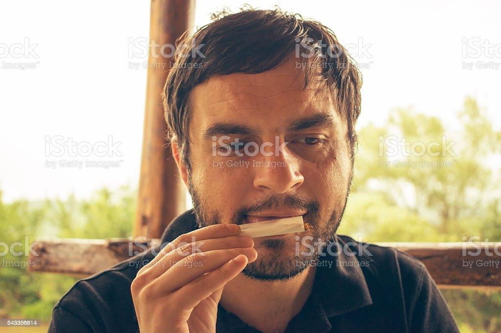 Young handsome man with short hair rolling a cigarette stock photo