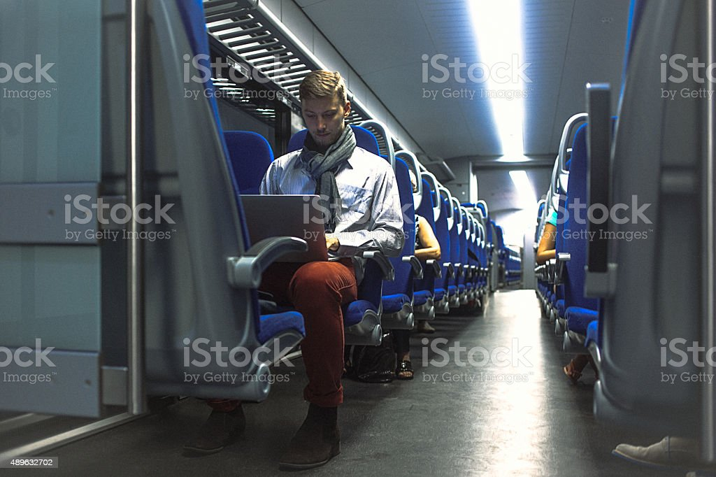 Young handsome man working on laptop while commuting to work stock photo