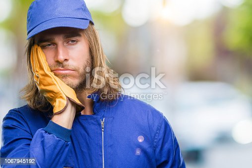 istock Young handsome mechanic man with long hair over isolated background thinking looking tired and bored with depression problems with crossed arms. 1067945192