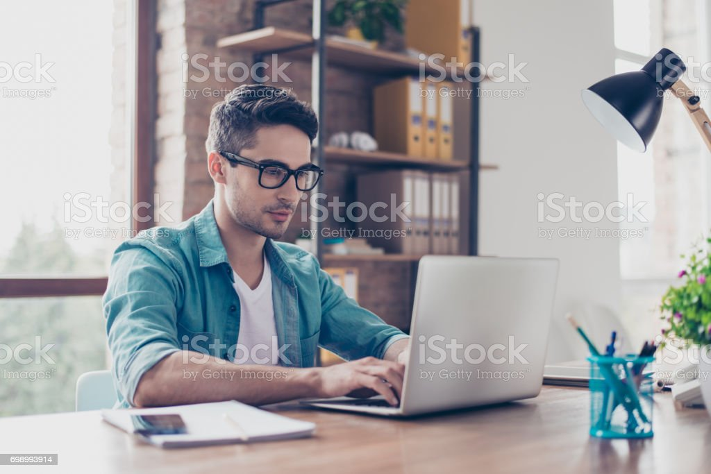 Young handsome minded man in jeans shirt and spectacles sitting at the table and typink a letter to his  acquaintance stock photo